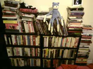 many books on shevles and stacked on the floor.